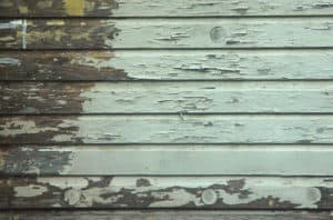peeling paint due to moisture on wood siding on an old house
